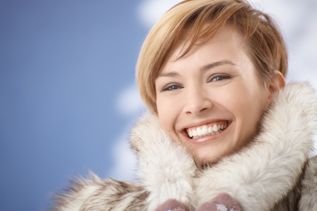 gingerish: Portrait of happy young woman wearing fur coat on a sunny winter day.