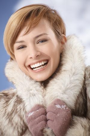 gingerish: Closeup portrait of happy, laughing young woman wearing fur coat Stock Photo