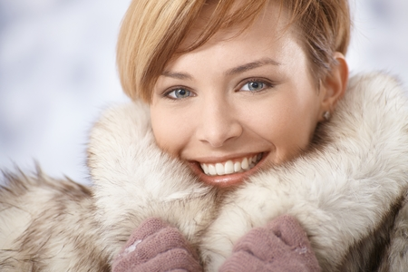 woman short hair: Closeup portrait of attractive young woman wearing warm fur coat in winter.