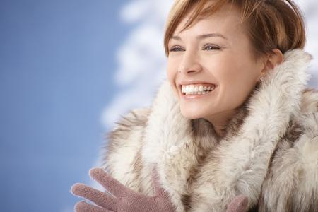 gingerish: Portrait of happy young woman wearing fur coat, enjoying winter sunshine.