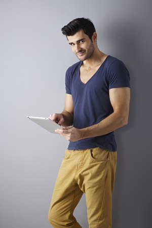 Athletic young man standing against wall, using tablet, smiling, looking at camera. photo