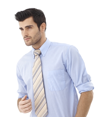 bristly: Portrait of handsome young businessman in shirt and tie looking away.