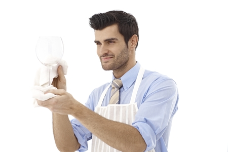 Happy male wine-expert polishing wine glass. Stock Photo