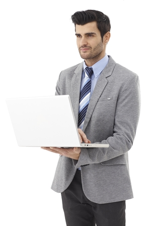 Young businessman holding laptop computer in hand, working on it. photo