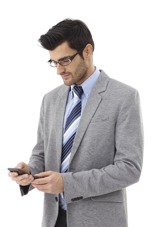 Young businessman writing text message on mobilephone. photo