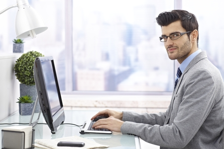 Young businessman sitting at desk in office, working on computer, looking at camera.