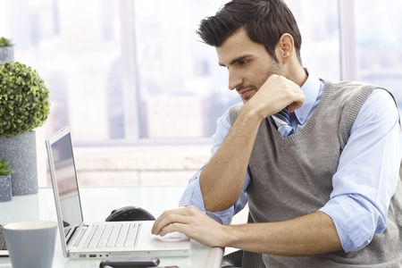 man working: Young man sitting at desk in office, working on laptop computer.