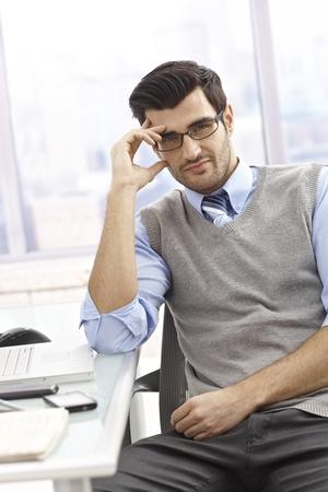 jornada de trabajo: Retrato de trabajador de oficina casual, sentado en el escritorio en la Oficina brillante, sonriendo.