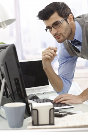 vertical image: Young businessman working with computer in office.
