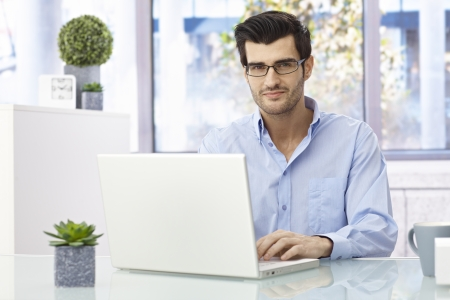 Handsome young businessman sitting at desk, working on laptop computer, looking at camera, smiling. Imagens