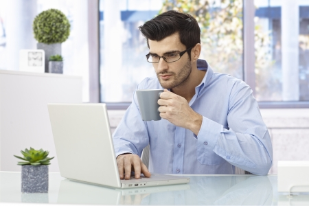 Young man sitting at desk at home, working on laptop computer, drinking coffee. Imagens