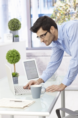 Young businessman using laptop computer standing at desk, leaning on it. photo