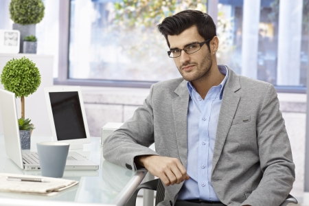 Portrait of handsome young businessman in glasses, sitting at desk, resting arm on desk, looking at camera. photo