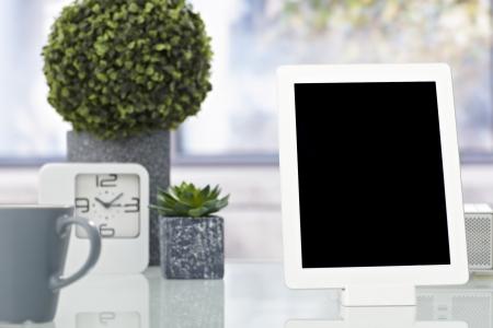 objeto: Foto de detalle de la computadora de la tableta colocada en el escritorio ordenado.