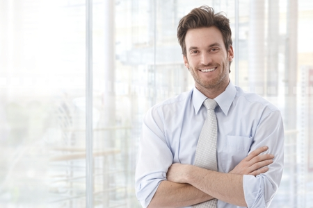 young unshaven: Portrait of handsome confident young businessman standing arms crossed, smiling happy, looking at camera.