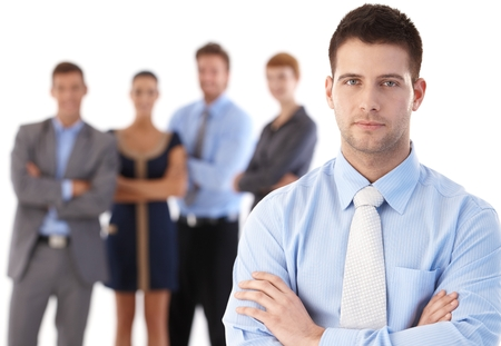 Portrait of confident young businessman standing arms crossed, team behind. Stock Photo - 22601800