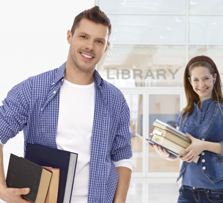 Male college student holding books at library, smiling, looking at camera. photo