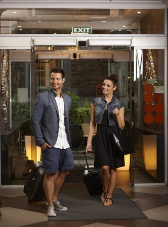 Happy young couple arriving at hotel with suitcases. photo