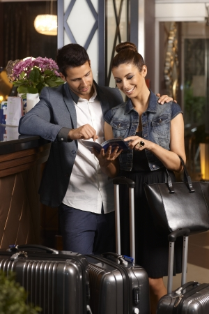 guests: Happy young couple looking at sightseeing catalogue upon arrival at hotel lobby, surrounded by suitcases.
