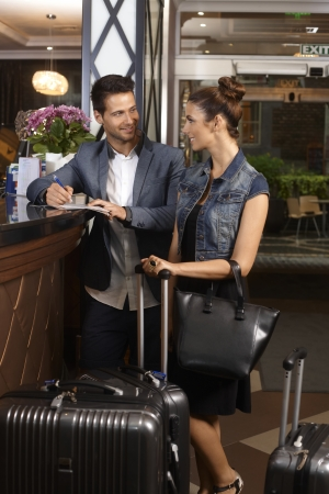 guests: Young couple filling in check in form at hotel reception upon arrival, smiling happy. Stock Photo