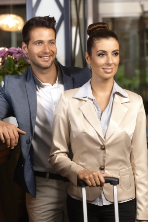 Young couple smiling happy, looking away at hotel reception desk upon arrival. photo