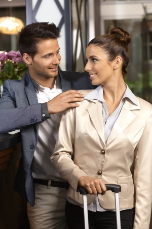 reception counter: Loving couple standing at reception desk upon arrival at hotel, smiling happy. Stock Photo