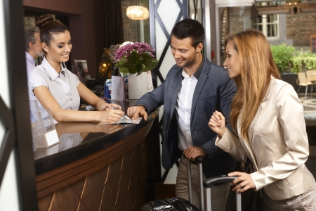 Receptionist giving tourist information to hotel guests upon arrival. Imagens