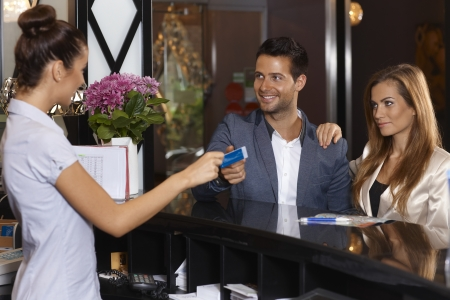 Receptionist giving key card to new guests at hotel, smiling happy. Imagens