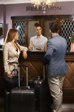 Receptionist giving information to new guest upon arrival at hotel, surrounded by suitcases.