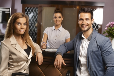 Portrait of happy young couple at hotel reception with receptionist. photo