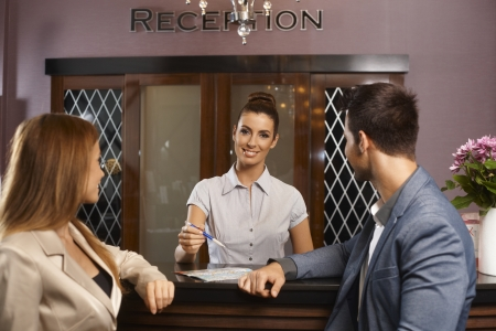 Portrait of happy female receptionist giving information to young couple. photo
