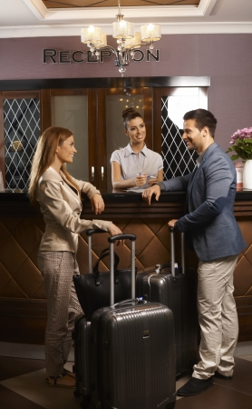 hotel reception: Happy young couple standing at hotel reception, checking in upon arrival, smiling.