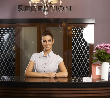 reception counter: Portrait of happy smiling female receptionist at hotel.