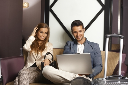 hotel lobby: Young couple sitting in hotel lobby, using laptop computer, smiling. Stock Photo