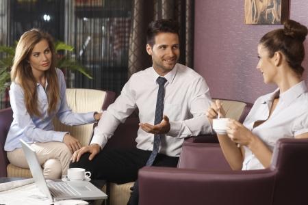 遅くまで働いて、ホテルのロビーやバーでラップトップ コンピューターを使用して、ディスカッションとコーヒーを持つ若いビジネスマンのチーム 写真素材
