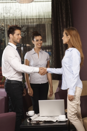 hotel worker: Business partners shaking hands at meeting in hotel lobby or bar.