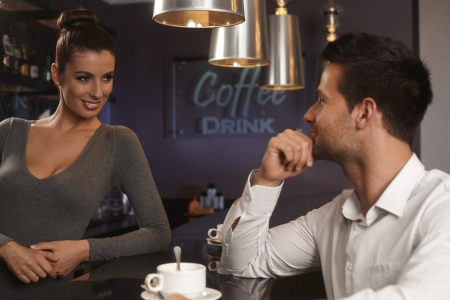 flirting: Pretty female bartender flirting with young man in bar, smiling. Stock Photo