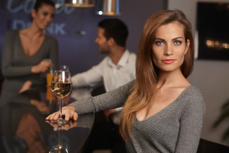 Portrait of beautiful young sexy woman sitting in bar, drinking wine. photo