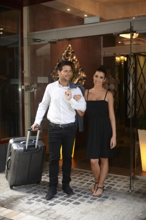 exiting: Young couple exiting hotel door, having suitcase, waiting for transfer.