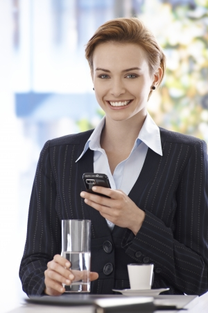 Portrait of happy young businesswoman using mobilephone, drinking water and coffee. photo