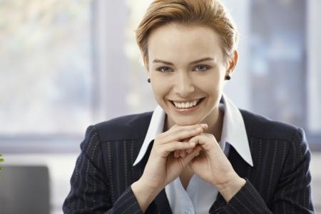 gingerish: Closeup portrait of beautiful young happy businesswoman, looking at camera. Stock Photo