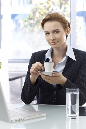 Attractive young businesswoman sitting at desk having computer, drinking coffee, looking at camera. photo