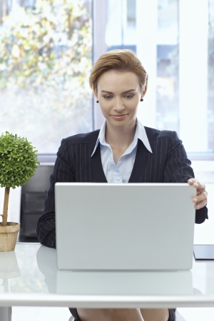 concentrating: Attractive businesswoman sitting at desk, working with laptop computer.