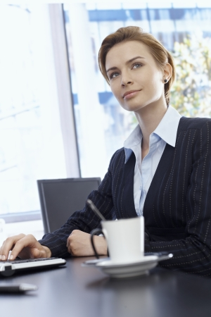Portrait of beautiful blonde businesswoman sitting at desk, looking away. photo