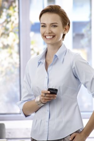 gingerish: Portrait of happy young businesswoman standing in office, holding mobilephone, looking away. Stock Photo