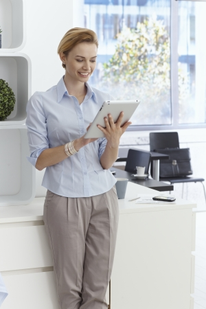 gingerish: Young woman using tablet computer, smiling, standing in office.
