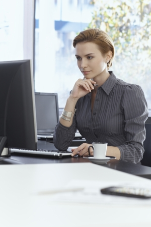 Young businesswoman sitting at desk in bright office, working with computer. Stock Photo - 22681757