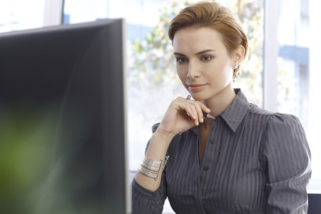 gingerish: Young businesswoman working with computer, concentrating.