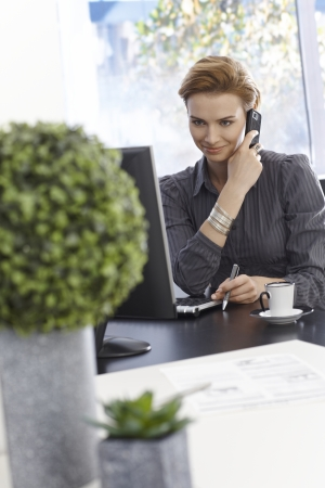 Smiling young businesswoman talking on mobilephone, sitting in green office. photo