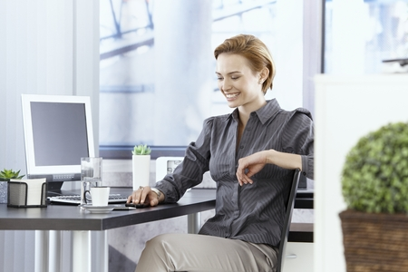 Happy young businesswoman sitting at desk in bright office. photo